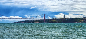 25ème d'April Bridge à travers le Tage et la vue de la ville d'Almada et de la statue de Jesus Christ, Portugal Image libre de droits