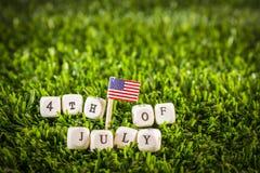 4ème du mot de juillet et du drapeau américain Images libres de droits