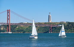 25ème du pont suspendu d'April Bridge au-dessus de la rivière Tejo avec Jesu Photos stock