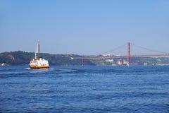 25ème du pont suspendu d'April Bridge au-dessus de la rivière Tejo avec le ferr Photo stock
