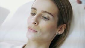 静脉扫描器在患者,关闭的面孔发光  招待会的女孩诊所的美容师的 股票录像