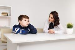 青少年的男孩谈话与他的治疗师社会工作者和患者 免版税库存照片