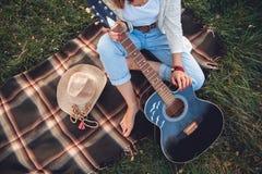 顶上的观点的有基于绿色草坪的吉他的美女 顶视图 库存照片