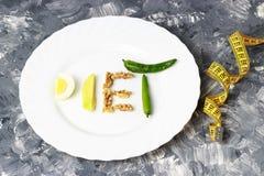 题字饮食由坚果、鸡蛋和鲕梨制成 在重量白人妇女的美好的腹部概念损失 免版税库存图片