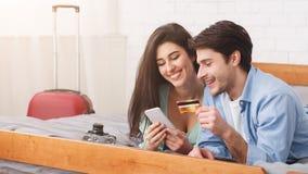 预定旅馆的新婚佳偶使用电话和信用卡 免版税库存图片