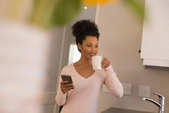 食用的妇女咖啡,当使用手机在厨房时 免版税库存照片