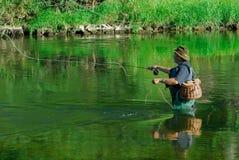 飞行渔夫在鳟鱼以后的河 免版税库存图片