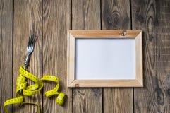 饮食概念、叉子和测量的磁带在木背景 叉子和测量的磁带在木背景一种健康生活方式的 库存图片