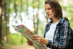 驾驶严肃的年轻女人看地图和,当远足通过豪华的绿色森林时 免版税库存照片