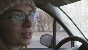 驾驶一辆汽车,在一个桃红色帽子和玻璃的年轻快乐的妇女 女孩,当驾驶,谈话到乘客,转动时 影视素材