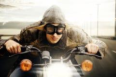 驾驶在路的年轻摩托车骑士 免版税库存照片