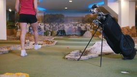高尔夫球微型使用 打微型高尔夫球的年轻女人户内 影视素材
