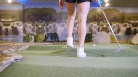 高尔夫球微型使用 打微型高尔夫球的年轻女人户内 来离球较近在孔附近 股票视频