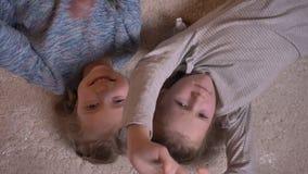 高兴地观看入照相机的两个小滑稽的女孩顶面被射击的画象说谎在地板上 股票录像