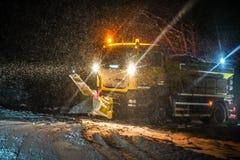 高速公路维护卡车在重的暴风雪期间的清洁路在夜,危险驾驶在冬天运输灾难期间 库存图片