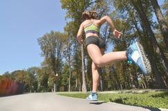 鲜绿色的体育胸罩和体育短裤的年轻白种人女运动员在夏天公园露天跑 夏天 免版税库存照片