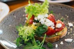 鲕梨多士用西红柿和希腊白软干酪 烘烤,吃 免版税库存图片