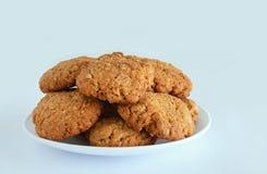 麦甜饼用谷物和种子在一块白色板材 奶油被装载的饼干 库存照片