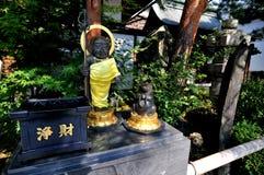 黑人菩萨和祈祷的浣熊雕象在Zenko籍寺庙的入口在日本 免版税库存照片