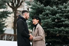 黑帽会议的俏丽的时髦的女孩走在冬天公园的 图库摄影
