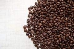 黑咖啡粒在轻的木桌,背景影像上说谎 安置文本 免版税库存图片