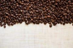 黑咖啡粒在轻的木桌,背景影像上说谎 免版税库存照片