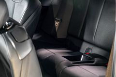 黑暗的豪华新的汽车内部 在现代汽车的后面乘客座位,侧视图 库存图片