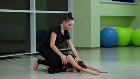 黑运动服的两位亭亭玉立的逗人喜爱的女孩姐妹艺术性的体操运动员做在健身房的准备和执行肌肉伸展运动 股票录像