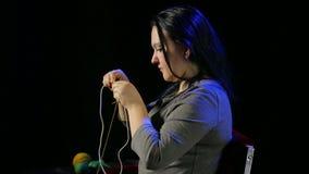 黑背景的妇女在黄色螺纹圆针编织  平均计划 影视素材
