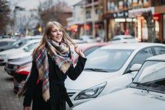 黑色大衣和围巾的年轻愉快的微笑的妇女走在城市附近的 等待她的男朋友 等待的会议 免版税图库摄影