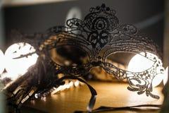 黑鞋带面具在浪漫大气的桌上 背后照明,特写镜头 免版税图库摄影