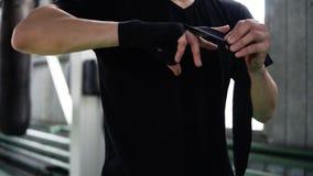 黑T恤杉立场的年轻男性拳击手在老牌健身房和包裹在他的手上的手黑色绷带 拳击袋子 股票录像