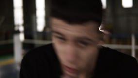黑T恤杉的年轻人履行在黑把装箱的绷带的打击和严肃看在健身房的照相机 关闭 影视素材