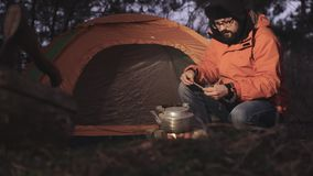 黄昏的一个游人在他的帐篷背景在森林里点燃火温暖在水壶的水 的treadled 股票录像