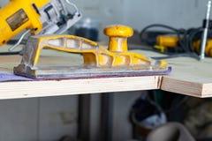 黄色沙纸和沙纸紫色颜色处理木头和的表面为绘做准备在建筑 免版税库存照片