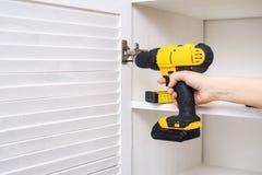 黄色螺丝刀在一只女性手上 家具铰链的设施在橱门的 库存图片