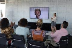 鼓掌企业的同事,当出席一视频通话在会议室时 免版税库存图片