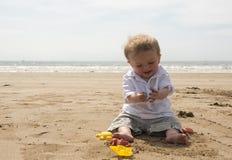Één éénjarige babyjongen het spelen met zand op het strand Royalty-vrije Stock Foto's