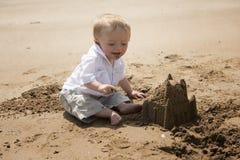 Één éénjarige babyjongen het spelen op het strand met een zandkasteel Stock Afbeeldingen