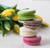Één of andere makarons gele tulpen en kop thee op de houten lijst springen de ochtend van de moedersdag op stock fotografie