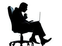 Één bedrijfs gegevensverwerking verraste zitting tussen mens en computer in armchai stock afbeelding