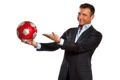 Één bedrijfsmensenholding die een voetbalbal toont royalty-vrije stock afbeelding