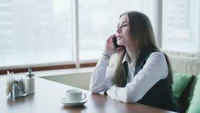 Één bedrijfsvrouw zit in een koffie en glimlacht en spreekt op de telefoon stock video
