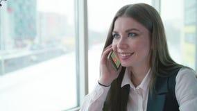 Één bedrijfsvrouw zit in een koffie en glimlacht en spreekt op de telefoon stock videobeelden
