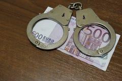 Één benaming van vijf honderd euro en politiehandcuffs liggen op een noot-gekleurde lijst Schending van de wet, corruptie, financ stock afbeelding