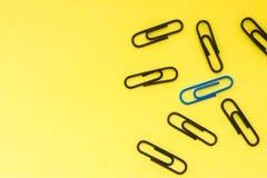 Één blauwe klem en vele zwarte klemmen op gele eenvormige mening als achtergrond van hierboven met duidelijk gebied van de helft  stock foto's