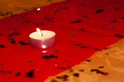 Één brandende kaars op een rood tafelkleed Ruimte op rechterkant Royalty-vrije Stock Foto's