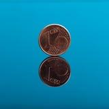 Één cent, Euro geldmuntstuk op blauw met bezinning Stock Afbeelding