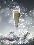 Één champagneglas en zilveren decoratie op een zilveren glanzende glit Royalty-vrije Stock Foto's