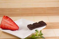 Één chocoladereep en één aardbei Stock Foto's